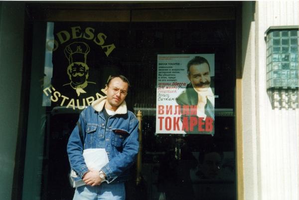 "Максим Кравчинский на фоне афиши несостоявшегося концерта В.Токарева и Б.Сичкина, у ресторана ""Одесса"", Брайтон-Бич, март 2002 года"